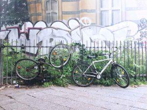 zwei fahrräder am Zaun vor Graffiti