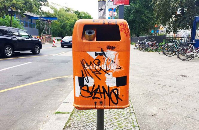 orangefarbener Mülleimer auf der Straße