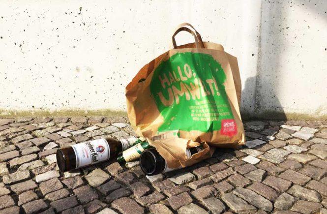 Papiertüte und Glasflaschen liegen auf dem Boden