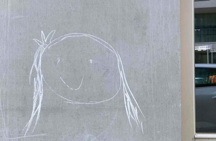 Lachgesicht Kinderzeichnung mit Kreide an Hauswand