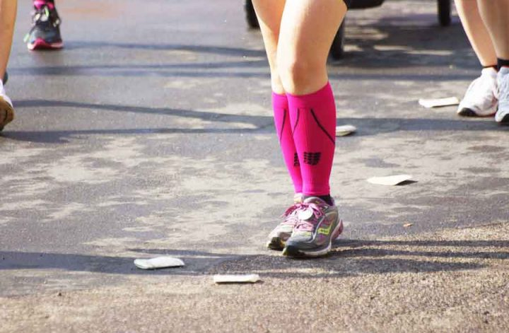 Beine mit pinkfarbenen Kniestrümpfen und Laufschuhen
